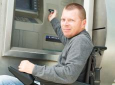 Gehandicapte man aan bankautomaat