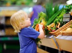 Kind neemt wortelen in supermarkt